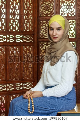 Young muslim woman holding a rosery in the mosque. - stock photo