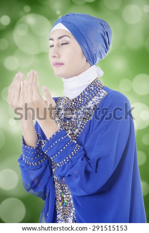 Young muslim woman in praying position while wearing a blue islamic clothes, shot with light glitter background - stock photo