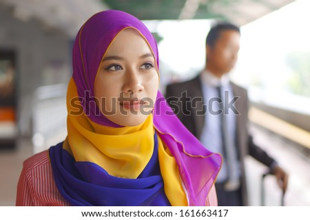 Young Muslim Woman Smiling, at the Train Station  - stock photo