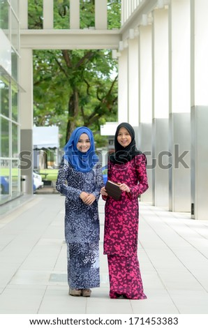 young muslimah discussing while walking at university - stock photo
