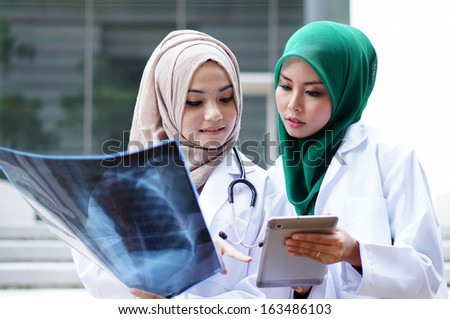 Young Muslimah doctor discussing about xray result - stock photo