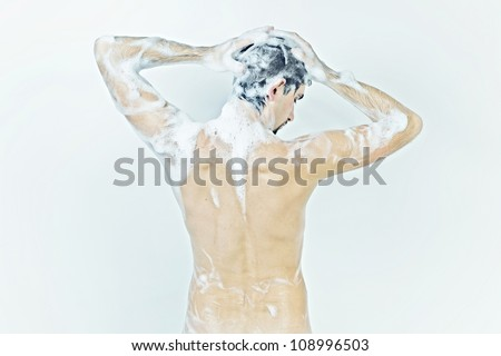 Young naked man taking a shower in the foam with a beautiful body on white background - stock photo