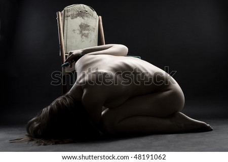 Young naked woman curling up on the floor in grief - stock photo