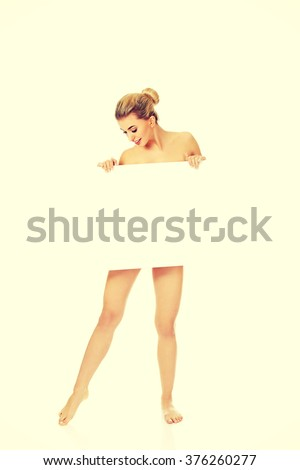 Young naked woman holding empty board. - stock photo
