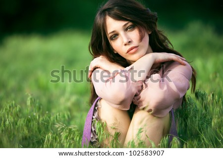 young natural looking woman relaxing in nature summer day - stock photo