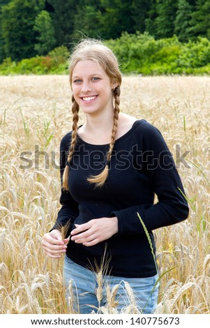 Young natural woman in a wheat field - stock photo