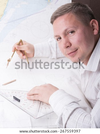 young navigator is measuring with divider and triangles on mercator navigation map - stock photo
