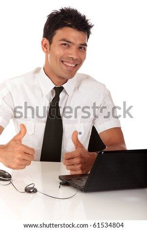 Young Nepalese businessman in office at desk in front of a laptop with the thumbs-up. Studio shot. White background - stock photo