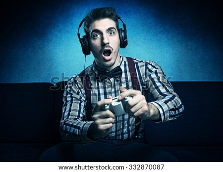 young nerd guy having fun with videogames  - stock photo