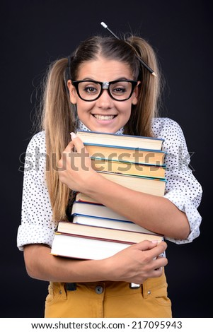 Young nerd woman crazy expression in glasses, holding book in hands on black background - stock photo