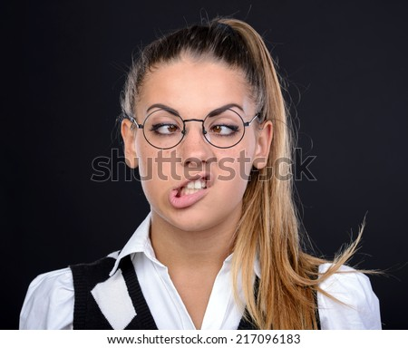 Young nerd woman crazy expression in glasses on black background - stock photo