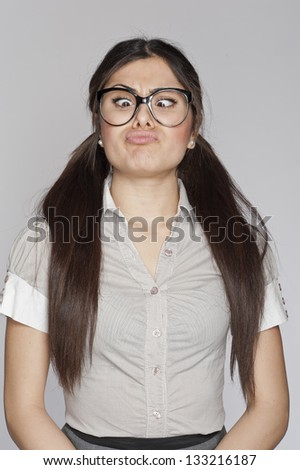 Young nerd woman crazy expression on white background - stock photo