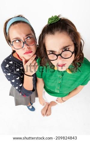 Young nerdy girls making faces and having fun. Studio shot. - stock photo