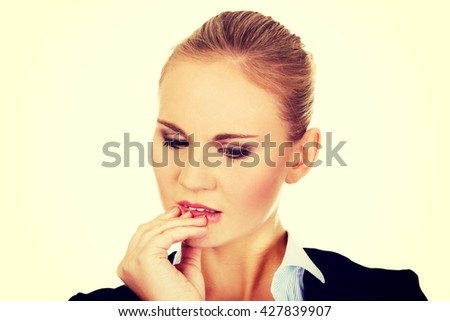 Young  nervous business woman biting her nails - stock photo