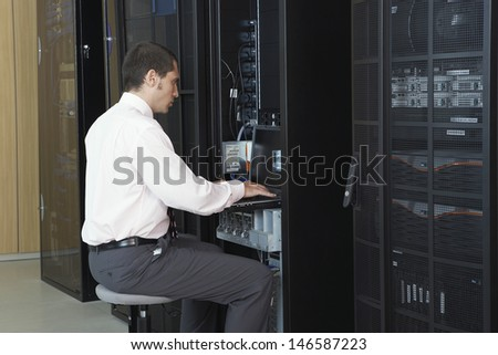 Young network engineer working in server room - stock photo