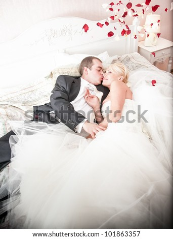 Young newly married couple lying on bed covered in rose petals - stock photo