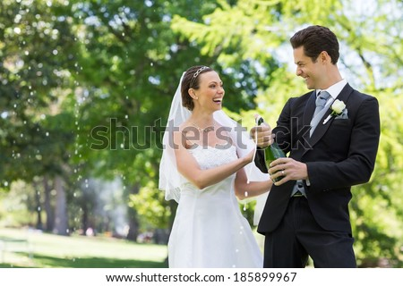 Young newlywed couple opening champagne bottle in park - stock photo
