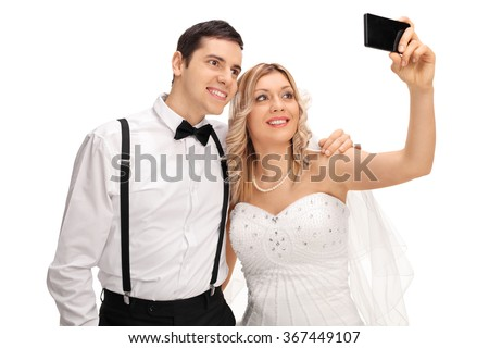 Young newlywed couple taking a selfie with a cell phone isolated on white background - stock photo