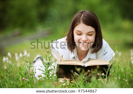 Young nice attentive woman lies on green grass and reads book at summer green park - stock photo