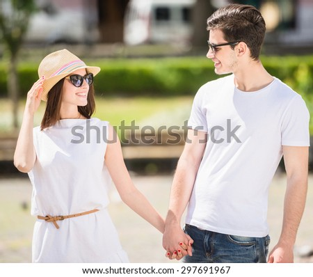 Young nifty couple walking along the street and looking to each other on sunny day. Front view. - stock photo