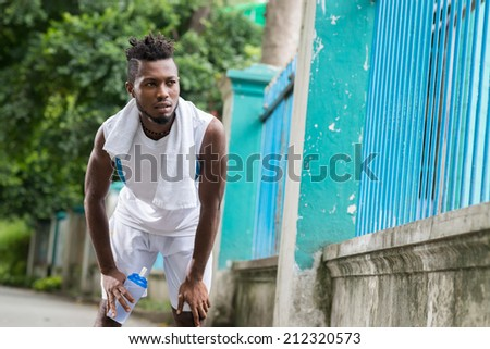 Young Nigerian man tired after jogging in the park - stock photo
