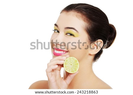 Young nude woman holding a lemon. - stock photo