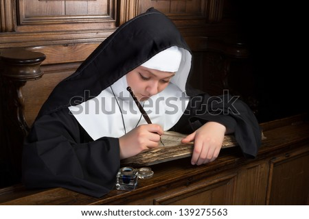 Young nun writing in an ancient book in a medieval church interior - stock photo
