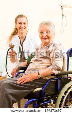 Young nurse and female senior in nursing home, the blood pressure is going to be measured - stock photo