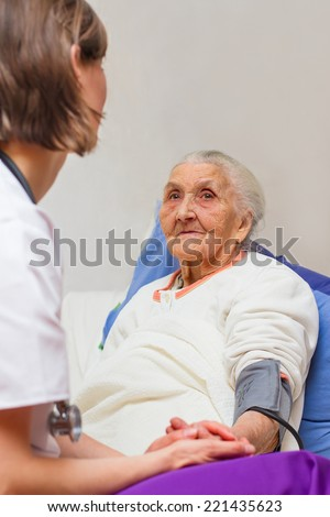 Young  nurse caring for  elderly patients helping their days in nursing home. - stock photo
