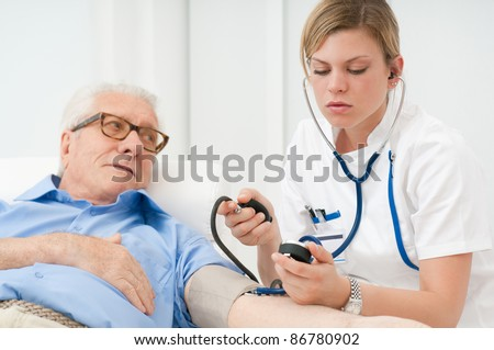 Young nurse checking the blood pressure of her old senior patient at hospital - stock photo