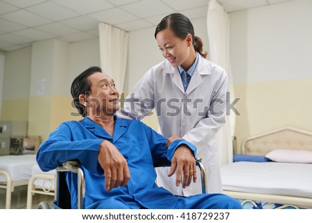 Young nurse comforting senior man in wheelchair - stock photo
