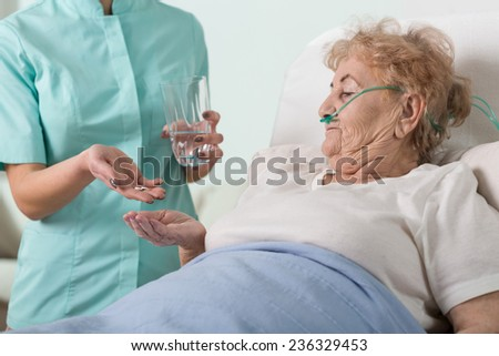 Young nurse giving the pills to sick aged woman - stock photo