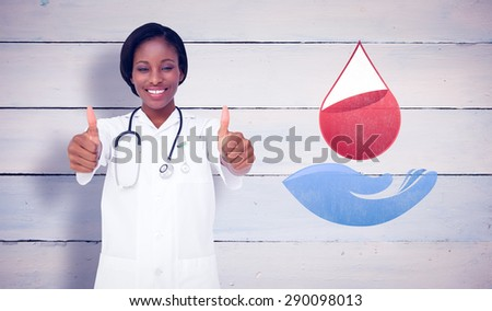 Young nurse giving thumbs up against painted blue wooden planks - stock photo