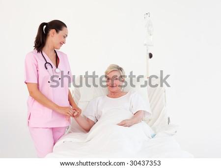 Young Nurse measuring an elderly patients Pulse - stock photo