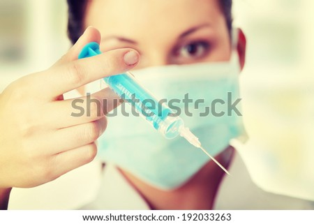 Young nurse or doctor in mask with syringe - stock photo