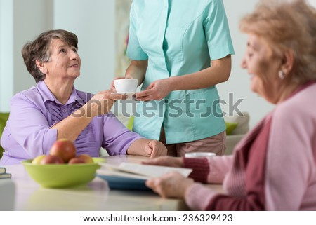 Young nurse serving the tea to two older women - stock photo