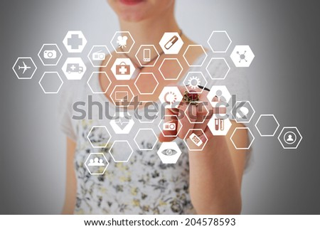 Young nurse standing and pressing modern medical type of buttons - stock photo