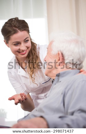 Young nurse taking care of an elder pensioner - stock photo