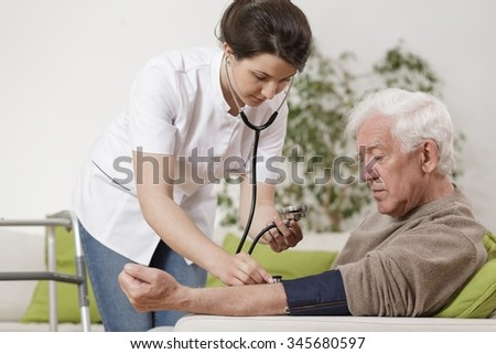 Young nurse taking old man's blood pressure - stock photo