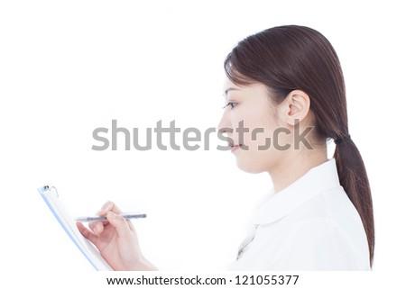 Young nurse writing chart, isolated on white background - stock photo