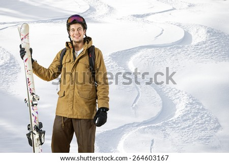 Young off piste skier standing in front of fresh tracks in the powder snow with skis in his hand - stock photo
