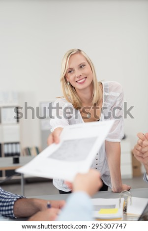 Young Office Woman in a Board Meeting, Passing a Business Document to Co-Worker with Happy Facial Expression. - stock photo