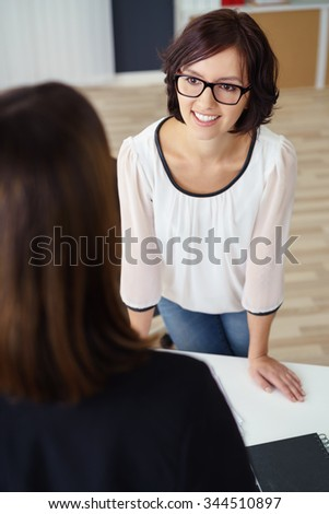 Young Office Woman Talking to her Female Colleague While Leaning Against the Table. - stock photo