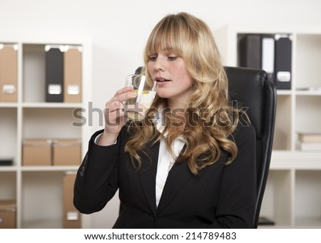 Young office worker enjoying a glass of water and slice of lemon as she sits at her desk against a backdrop of files on shelves - stock photo