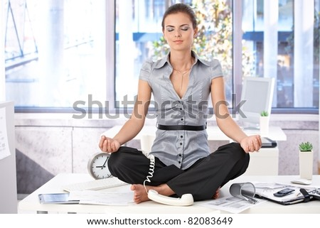 Young office worker meditating on top of desk in bright office.? - stock photo