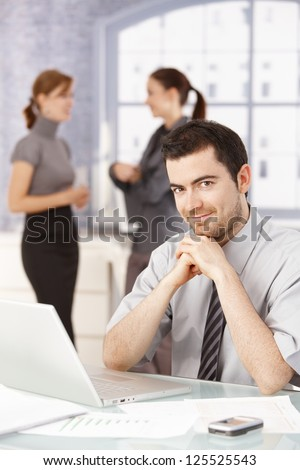 Young office worker taking a break in office, chatting. - stock photo