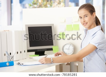 Young office worker woman sitting at desk, taking notes, smiling at camera.? - stock photo
