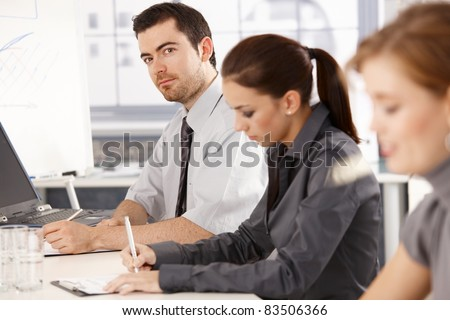 Young office workers having business training, sitting at meeting table, writing notes.? - stock photo