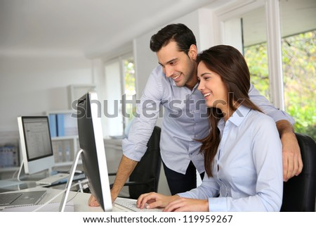 Young office workers in front of desktop computer - stock photo