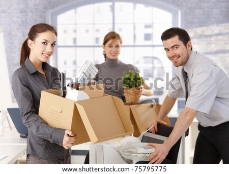 Young office workers moving office, unpacking boxes, smiling.? - stock photo